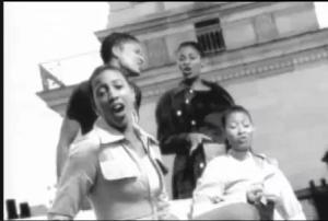 Черно-белый клип с поющими девушками на диване, стоящем на улице
